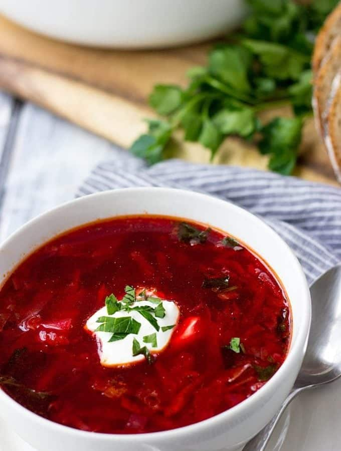 Ukrainian Borsch (Beet Soup) in a bowl with a dollop of sour cream and sprinkling of parsley.