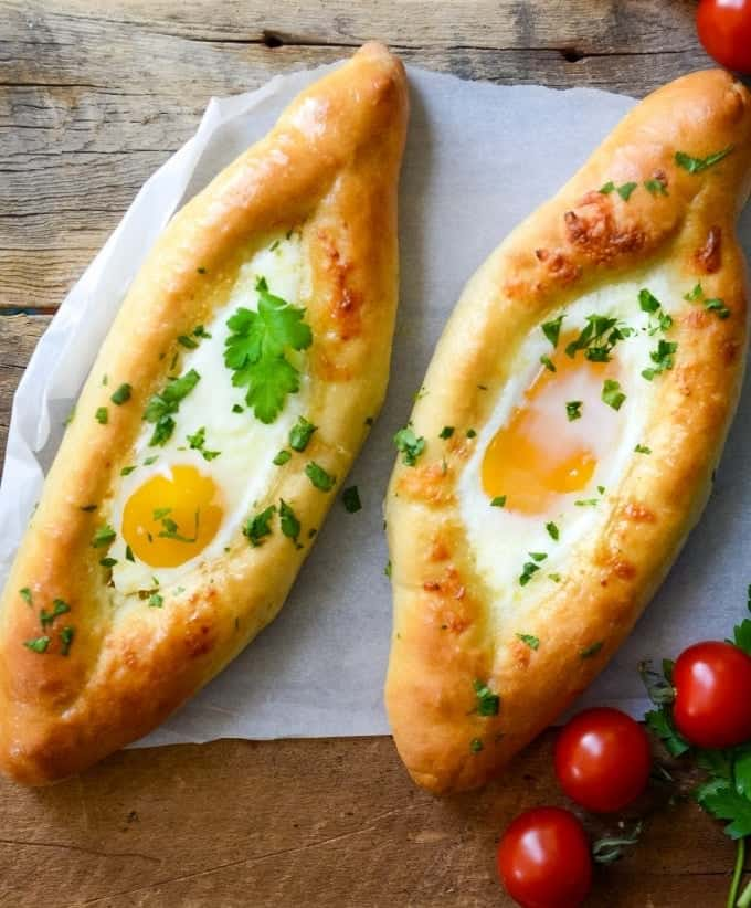 This Khachapuri recipe is a crowd-please. Get a step-by-step easy recipe of these delicious Khachapuri Adjaruli - traditional Georgian Cheese Flatbread topped with en egg.