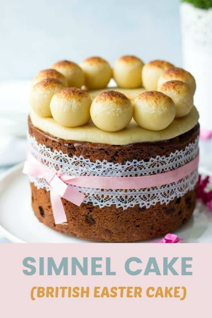 British Simnel Cake filled with dried fruits and topped with marzipan balls on a plate with pink and red flowers sprinkled around the cake.