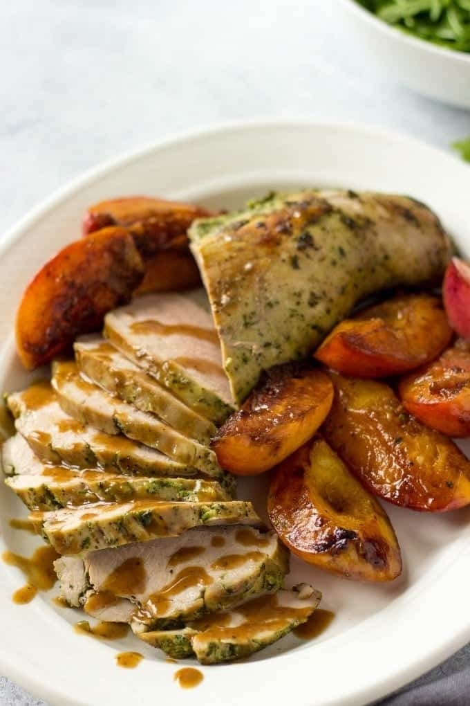 Sliced pork tenderloin with peaches and peach sauce on a serving plate.