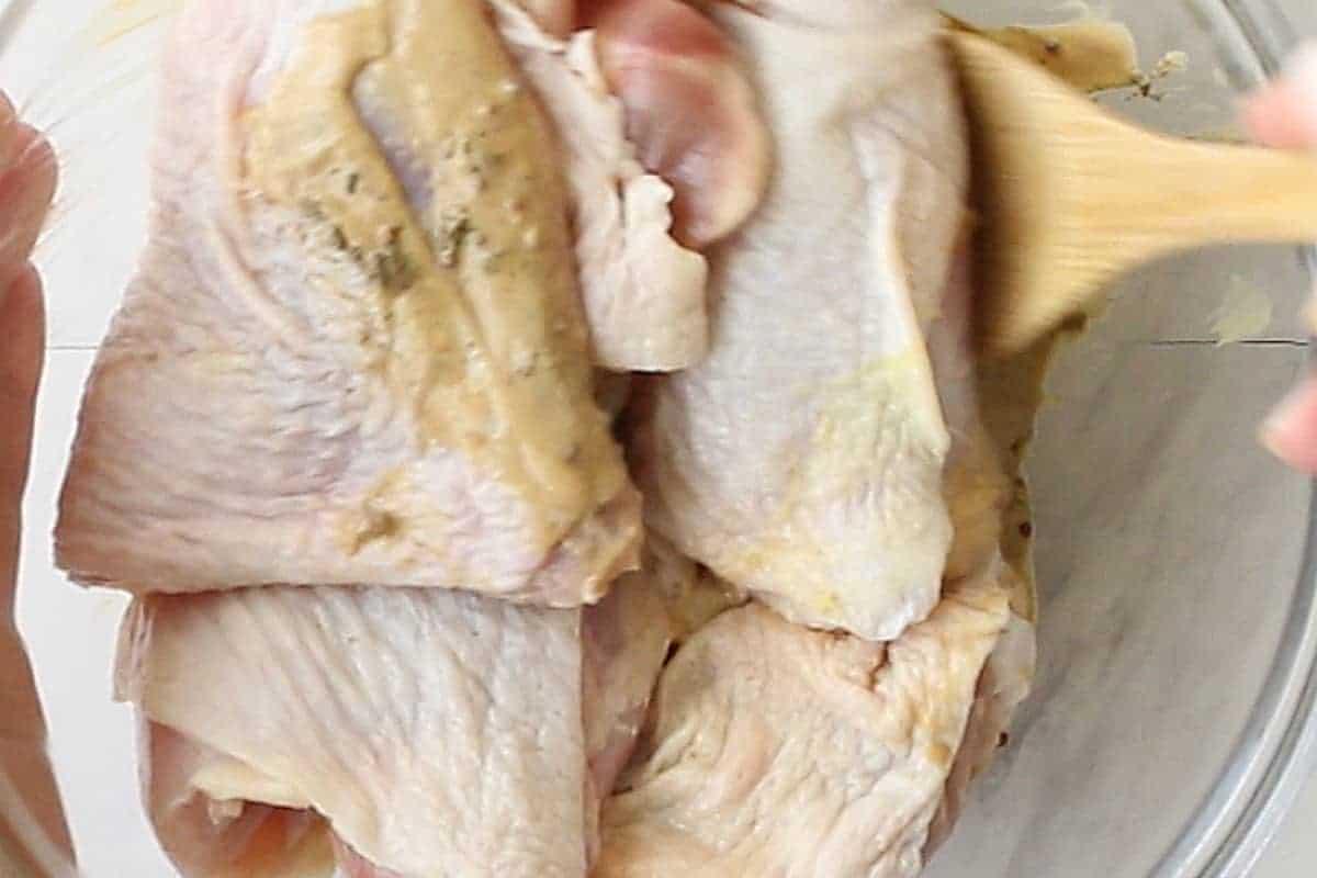 Coating chicken in mustard marinade