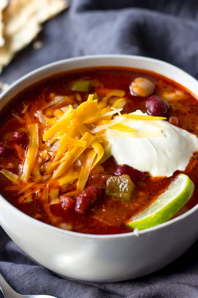 Slow Cooker Chili in a bowl with sour cream, shredded cheese and a piece of lime
