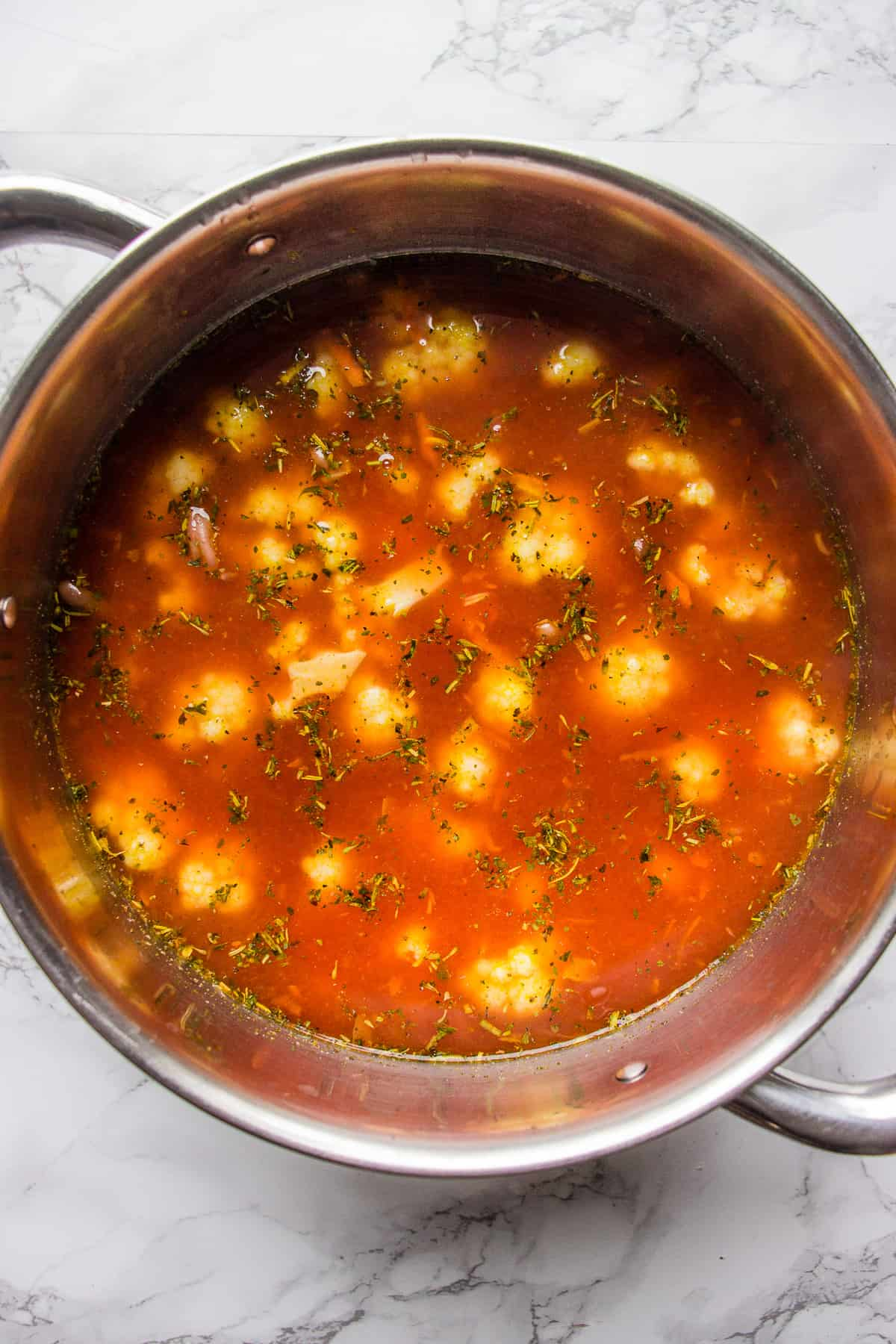Adding sauteed vegetables and cauliflower to a pot with a broth