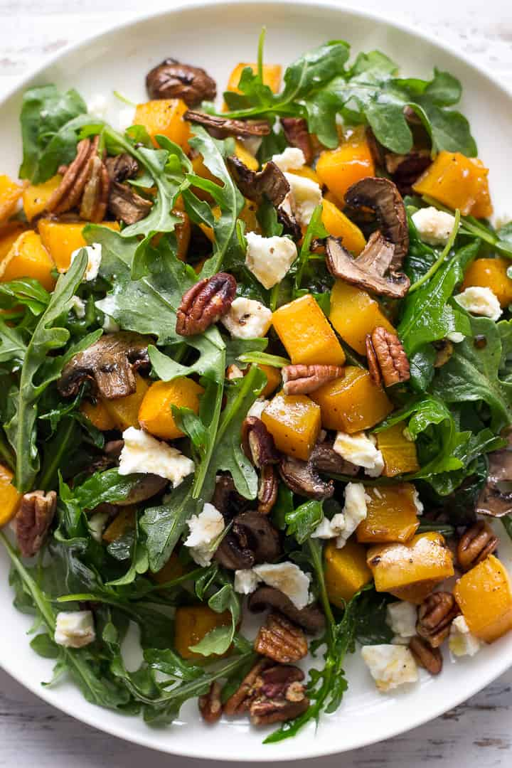 Warm Butternut Squash Salad with mushrooms, pecans and arugula on a plate