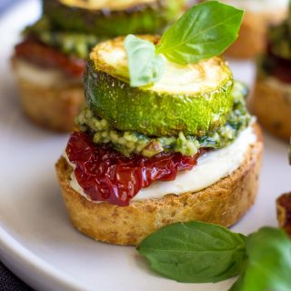 Bruschetta with cream cheese, sun-dried tomatoes, pesto and zucchini on a plate