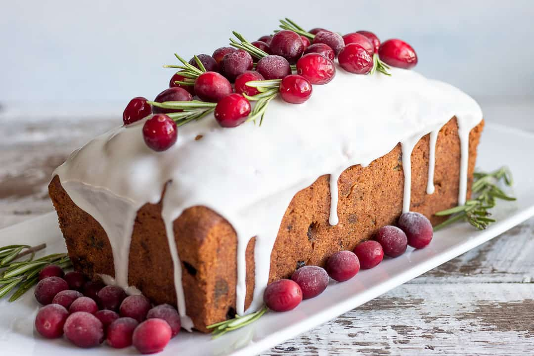 Christmas Cake on a platter decorated with frozen cranberries and rosemary sprigs
