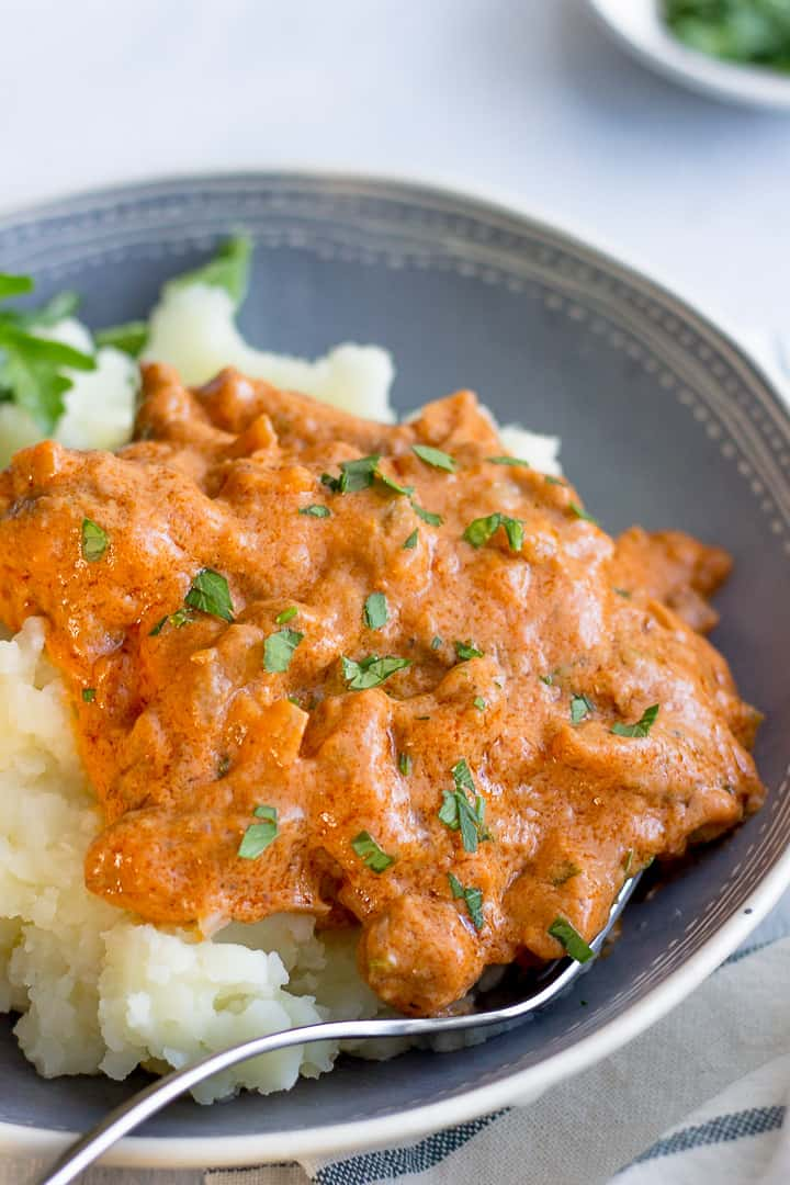 Creamy Beef Stroganoff made with sour cream on a plate with mashed potatoes and side greens