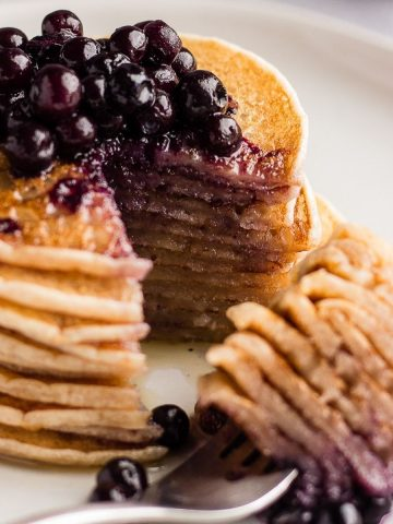 A stack of Cassava flour pancakes on a white plate served with blueberries on top
