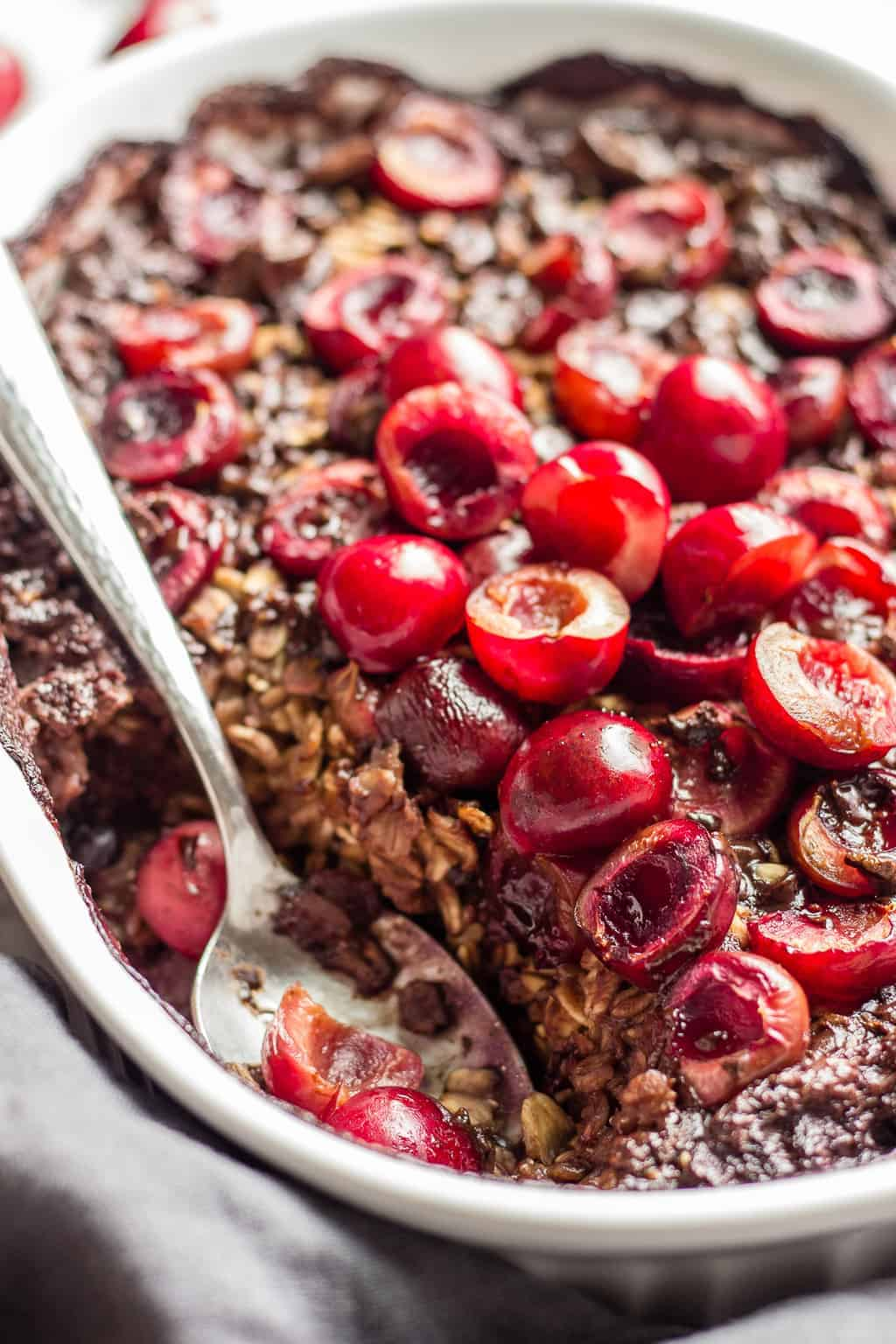 Spoon in a baking pan with chocolate and cherries baked oatmeal