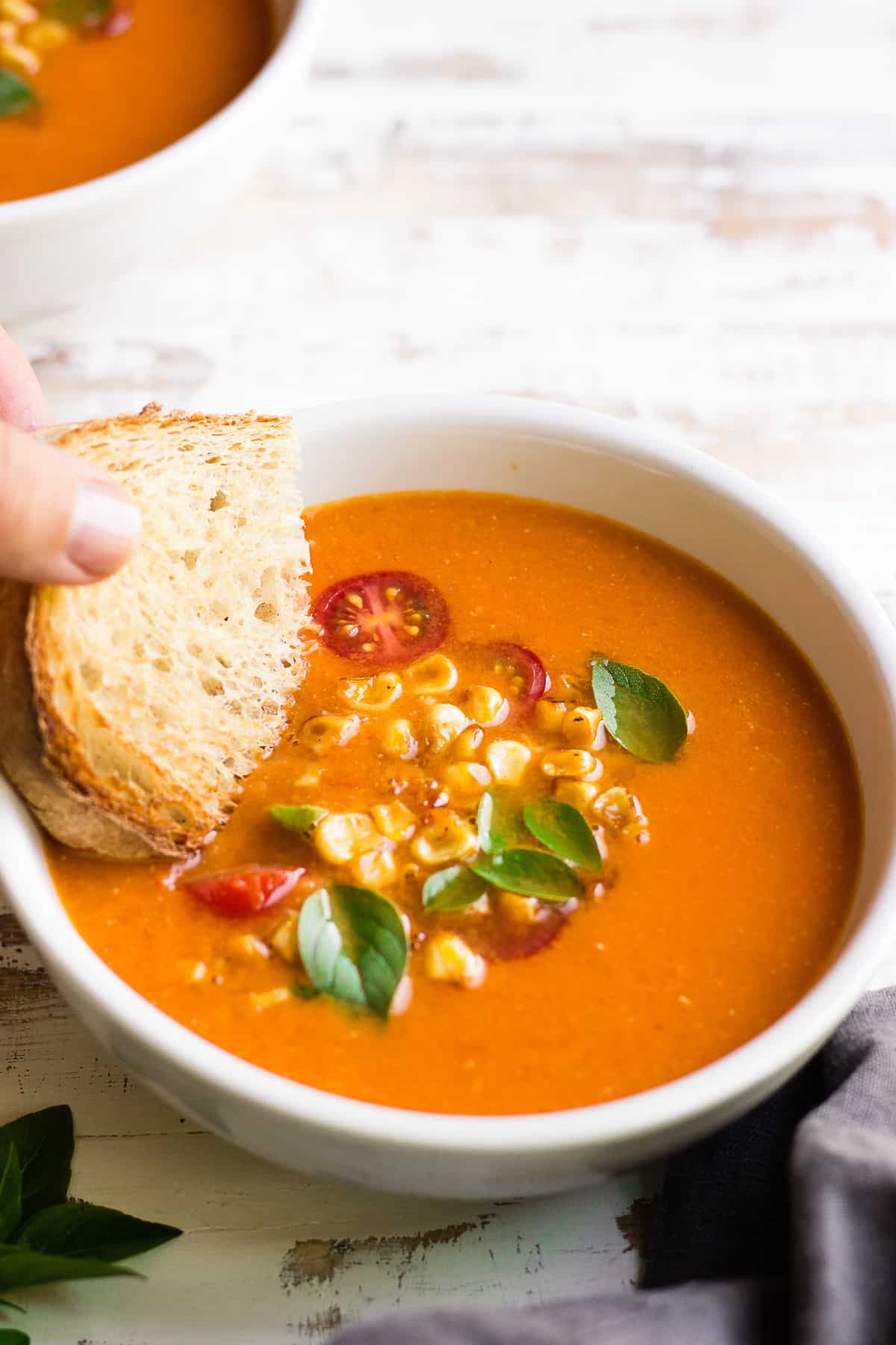 Easy vegan tomato soup in a bowl garnished with cherry tomatoes, basil and corn