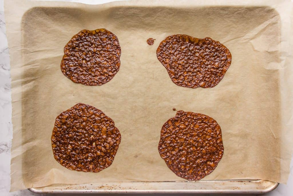 Baked brandy snaps on a baking sheet lined with parchment paper