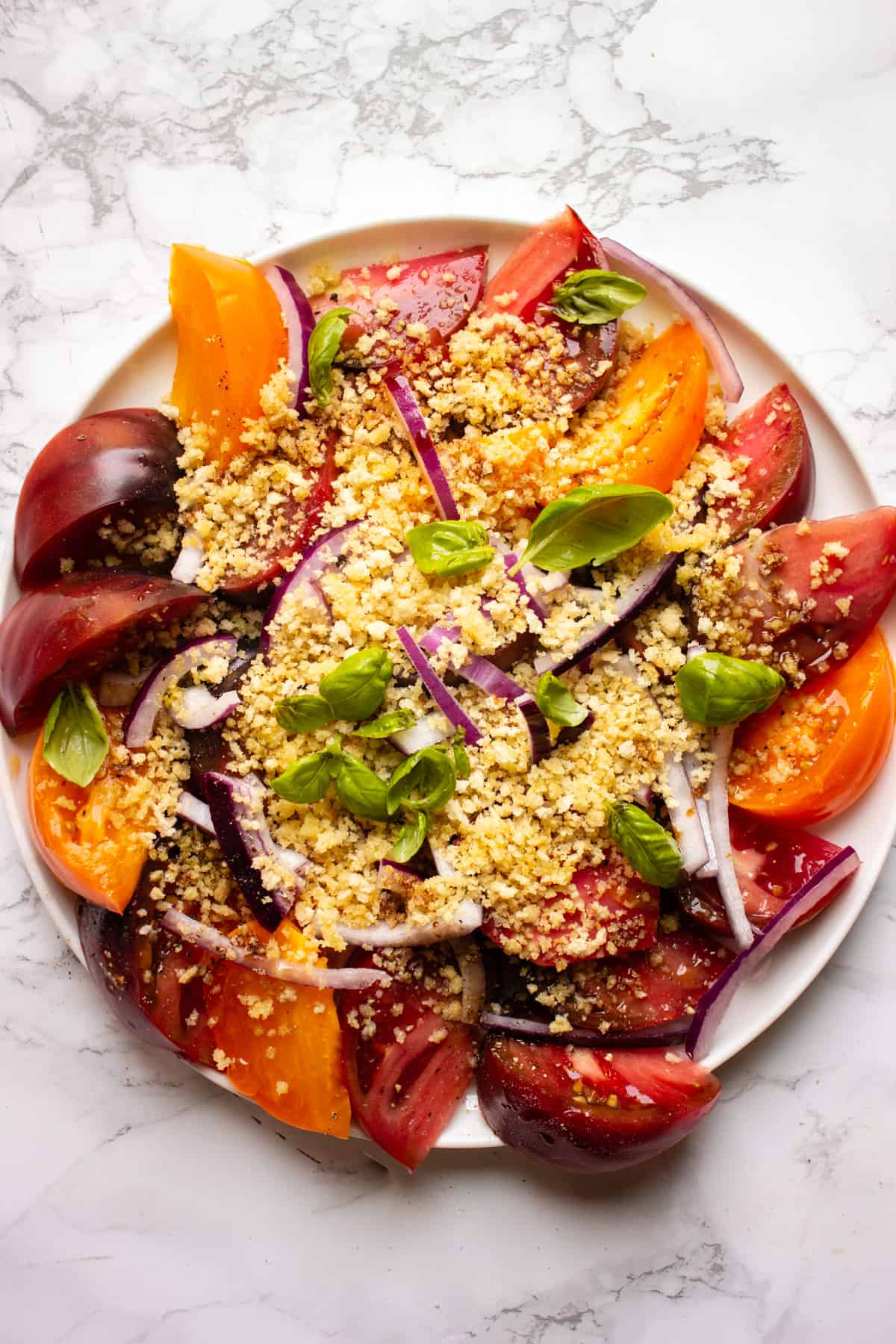 Fresh tomatoes with garlicky breadcrumbs on a white platter on a white background