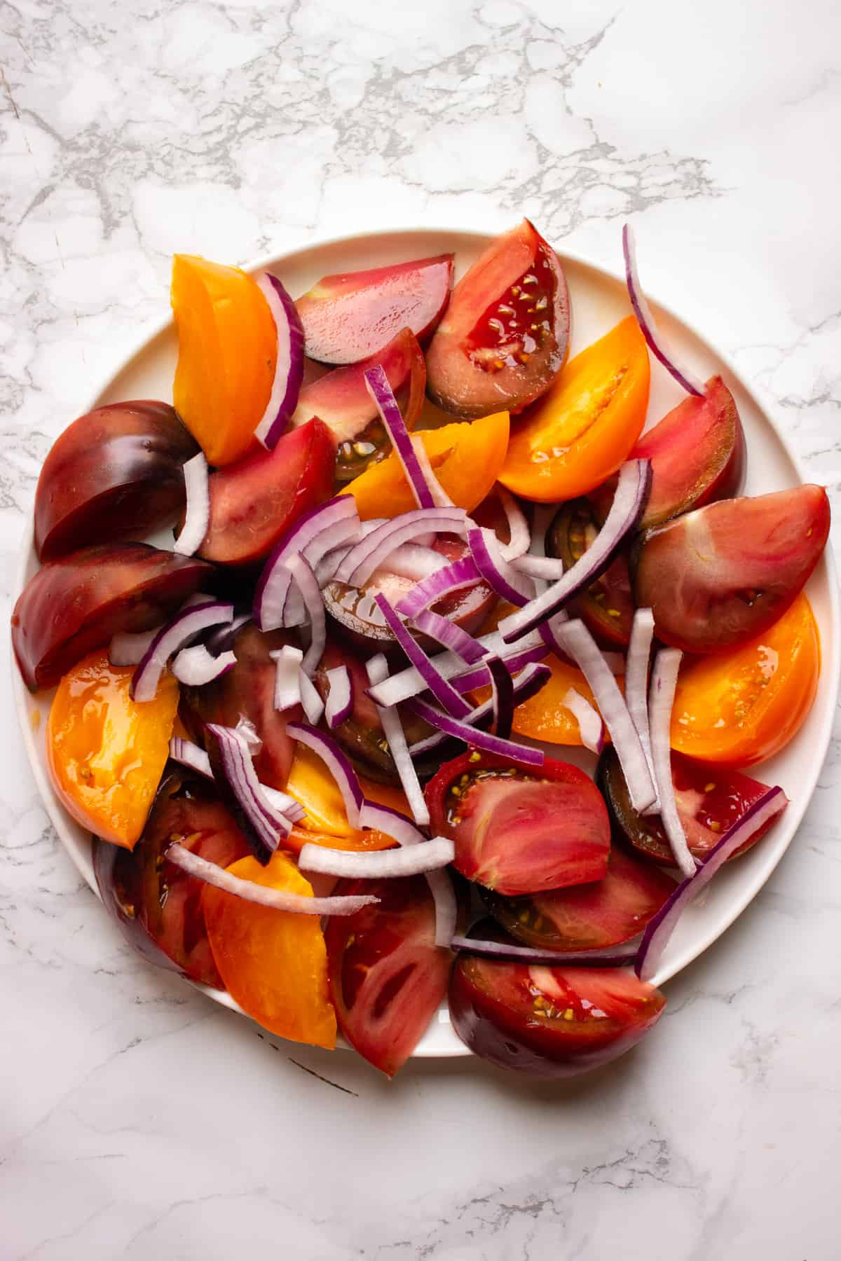 Wedges of heirloom tomatoes with sliced red onion on a plate on a white background