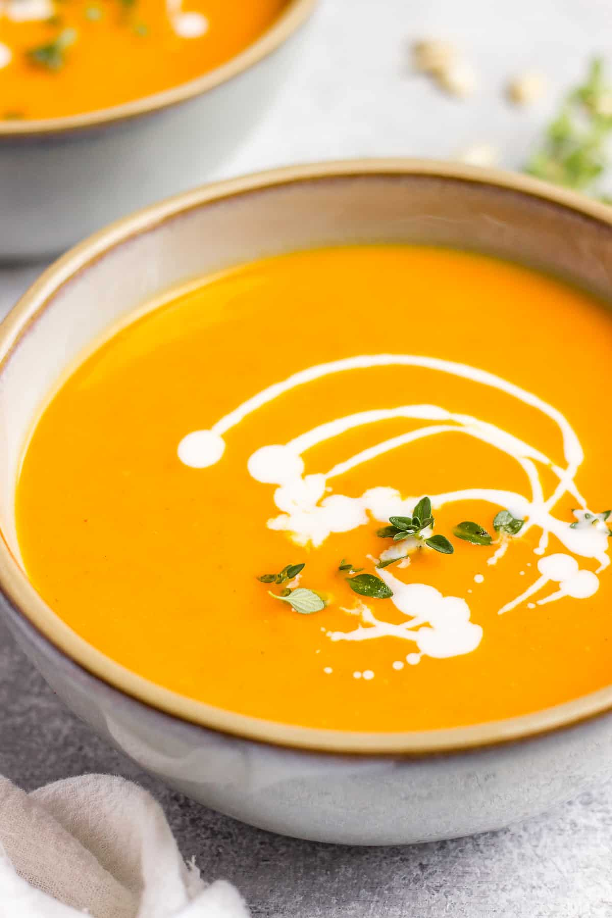 Creamy butternut squash soup with coconut milk in a bowl garnished with thyme