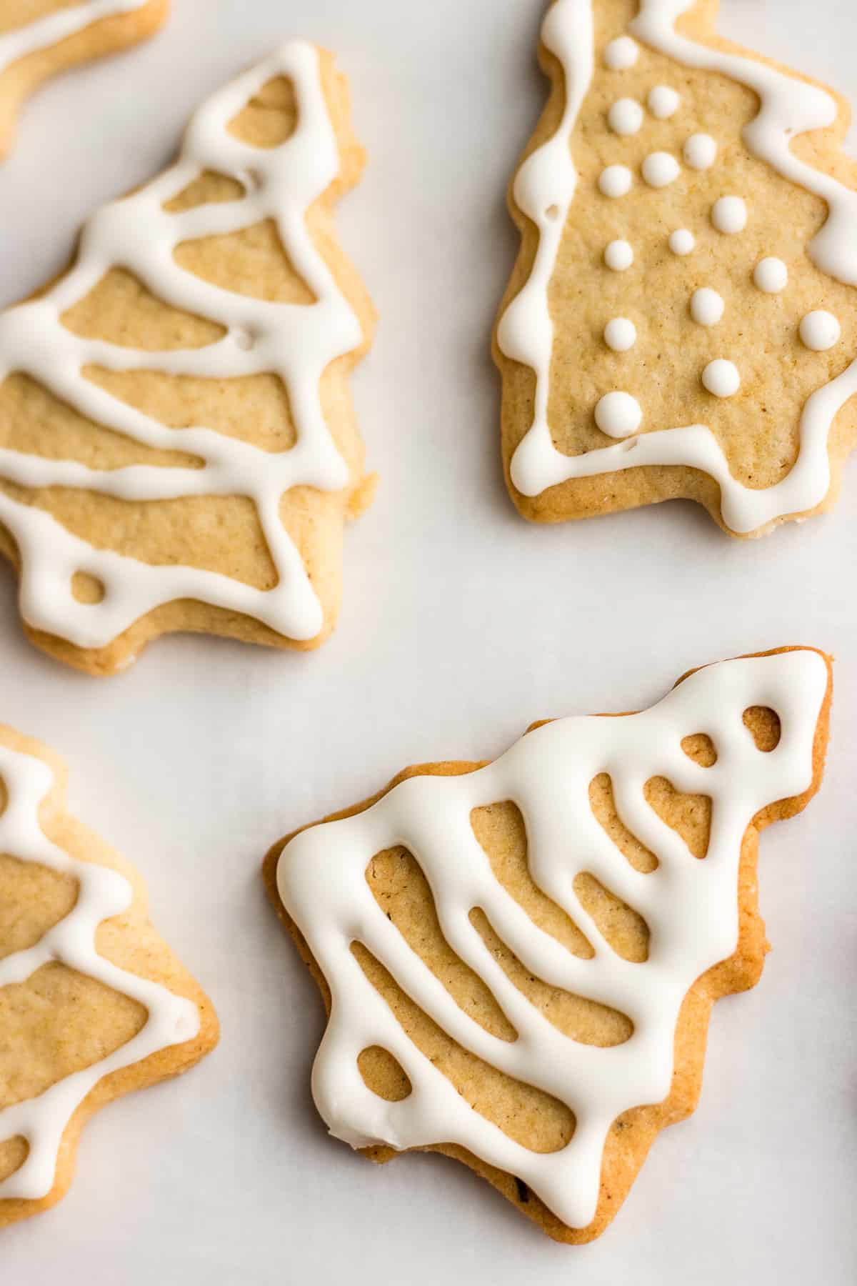 Vegan ginger spice cookies shaped like Christmas trees and decorated with icing