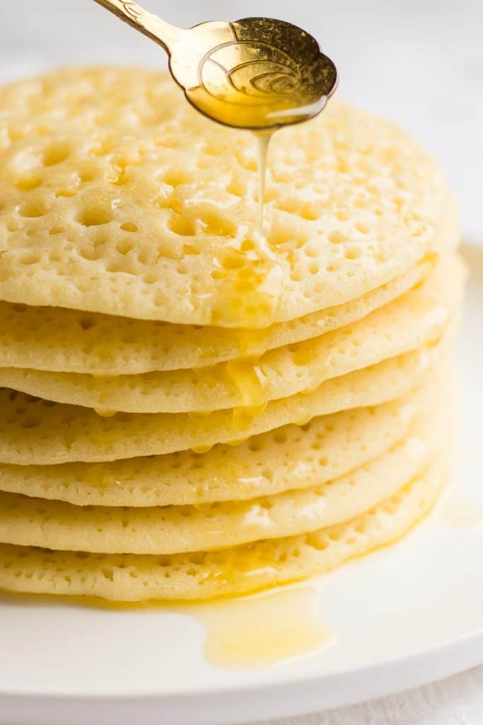 Drizzling of honey with butter over Moroccan pancakes