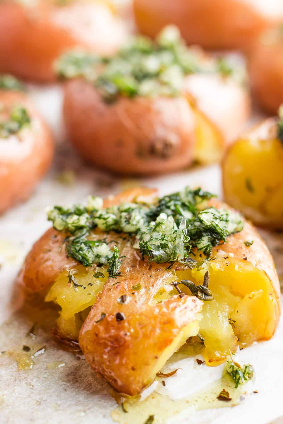 Smashed red potatoes with garlic sauce on a baking sheet