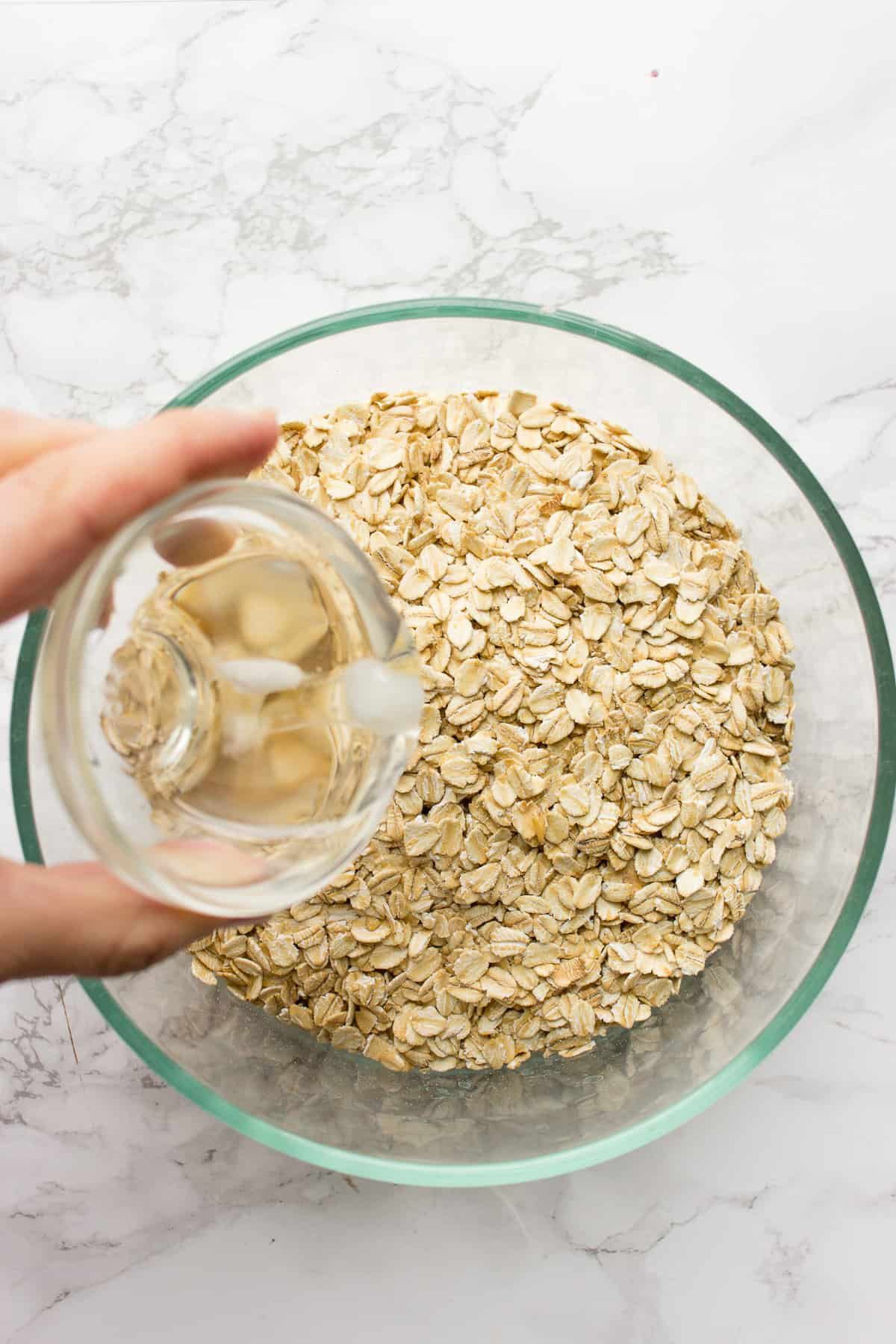 Pouring coconut oil over rolled oats