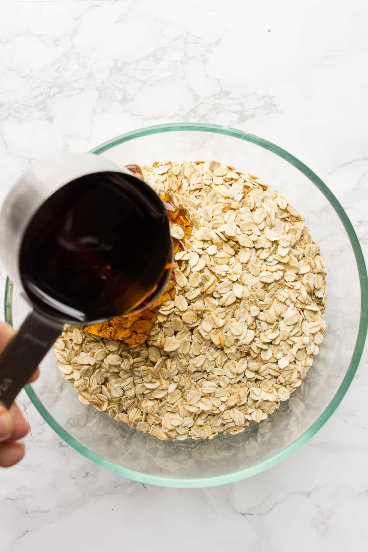 A large spoon pouring maple syrup into simple granola