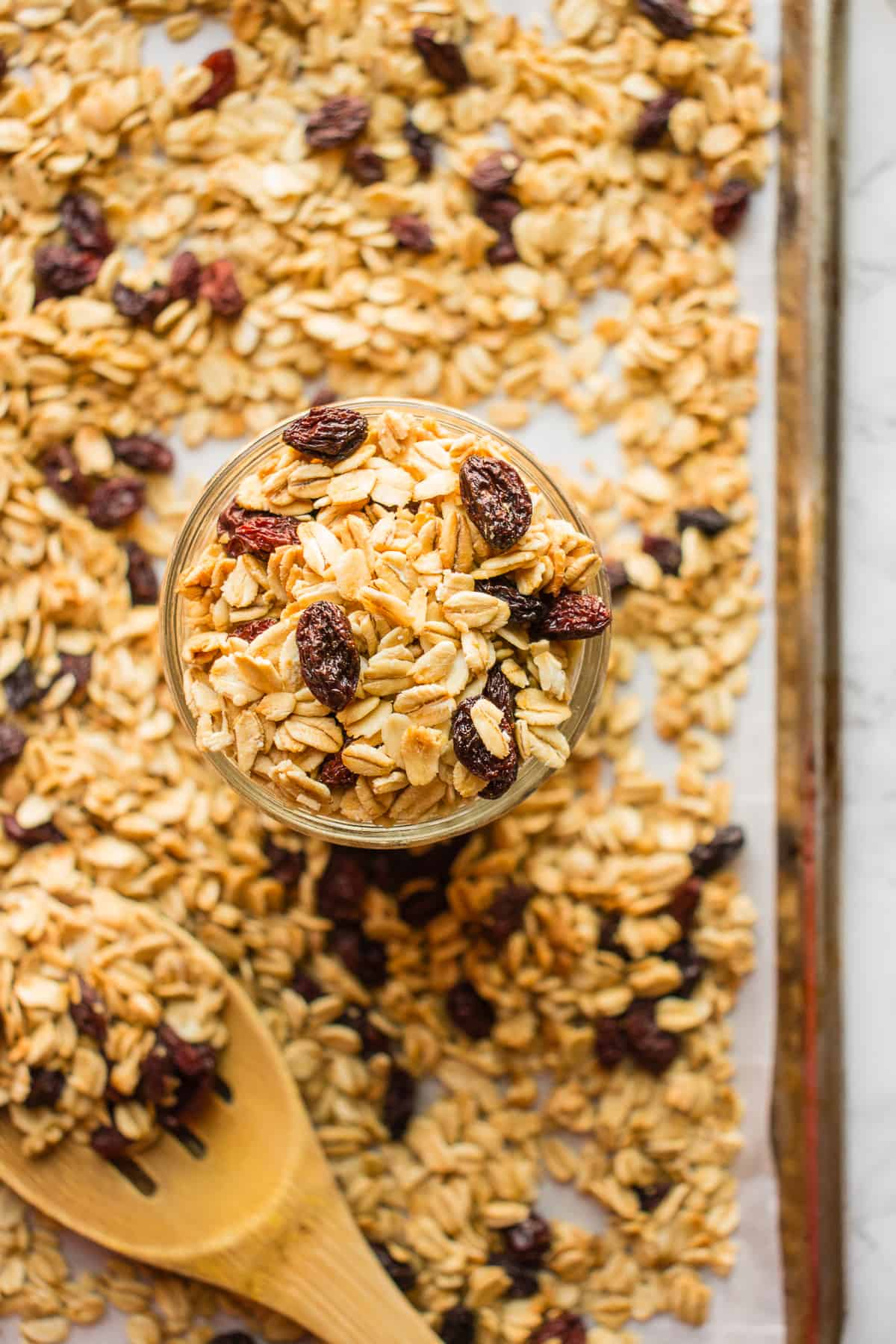 A baking tray covered with simple granola recipe and mason jar and wooden spoon