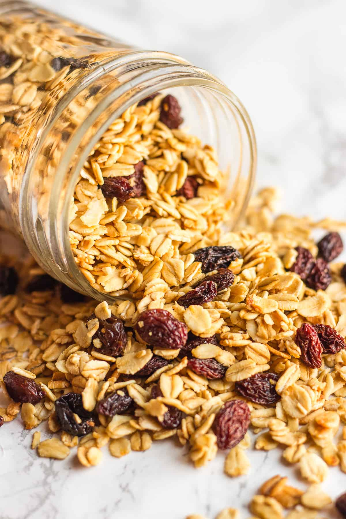 Simple granola pouring out of a mason jar onto a counter