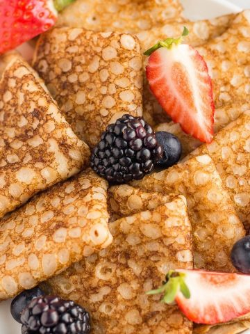 Vegan cassava flour crepes on a plate with berries