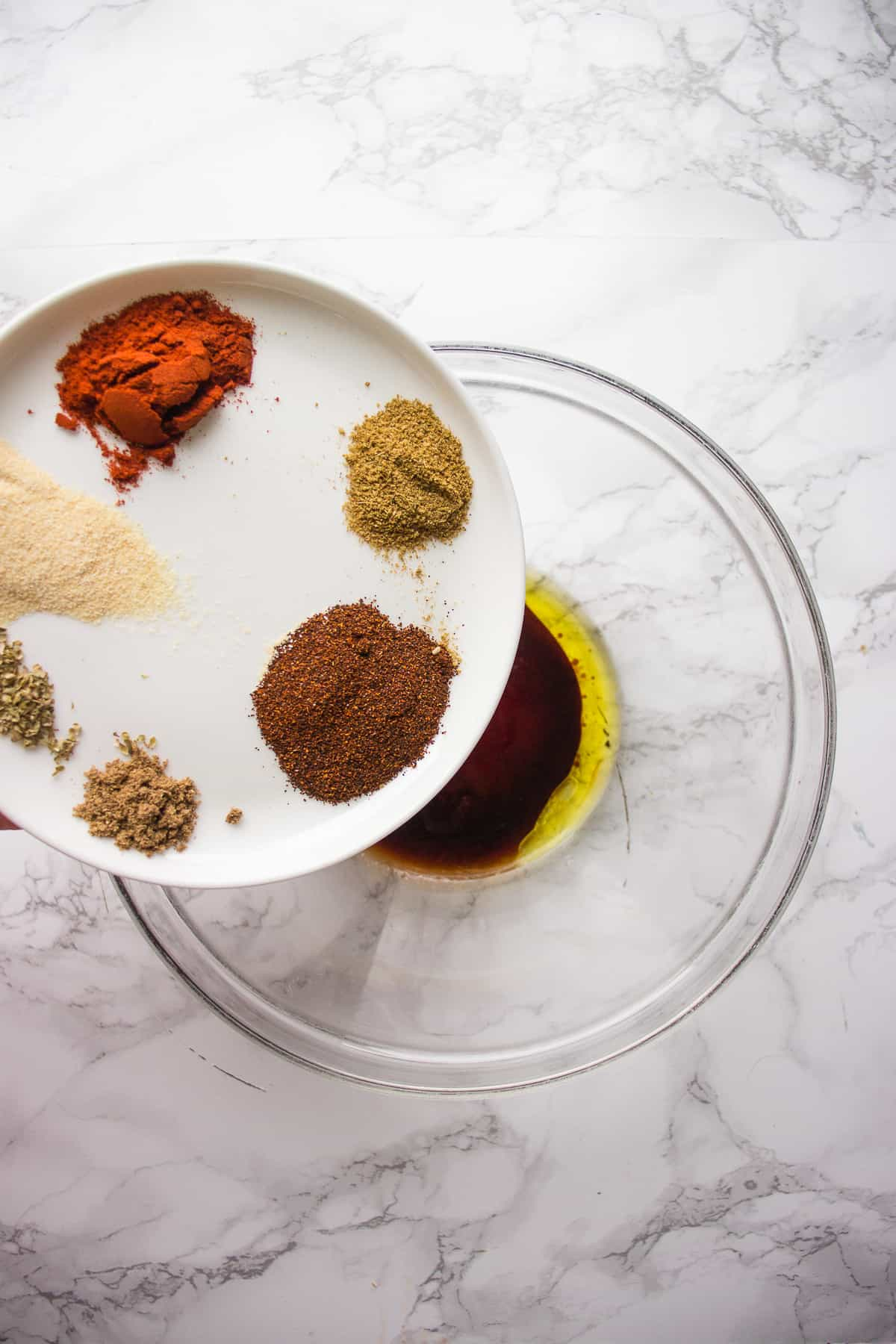 Combining taso seasoning in a glass bowl on a white background