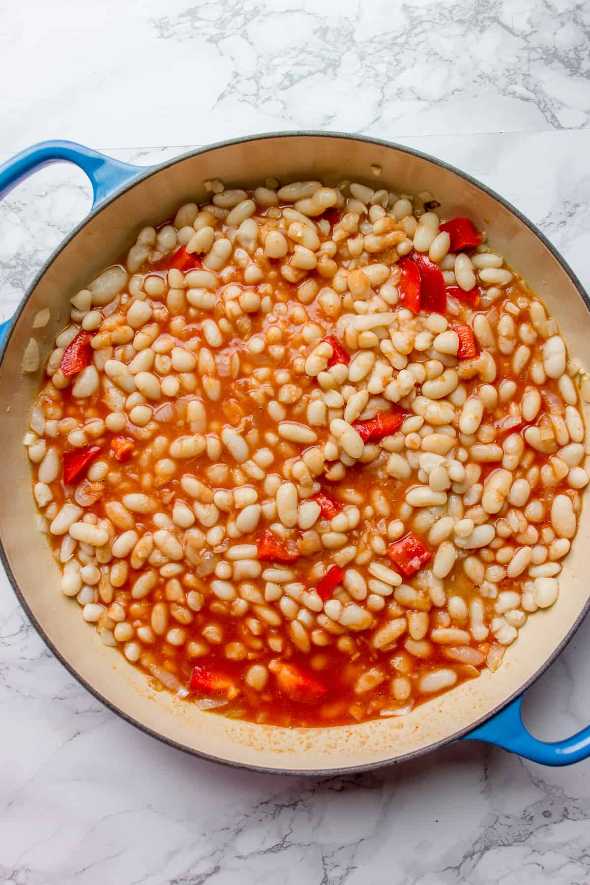 Adding tomatoes and bell peppers to a pot with cooked beans