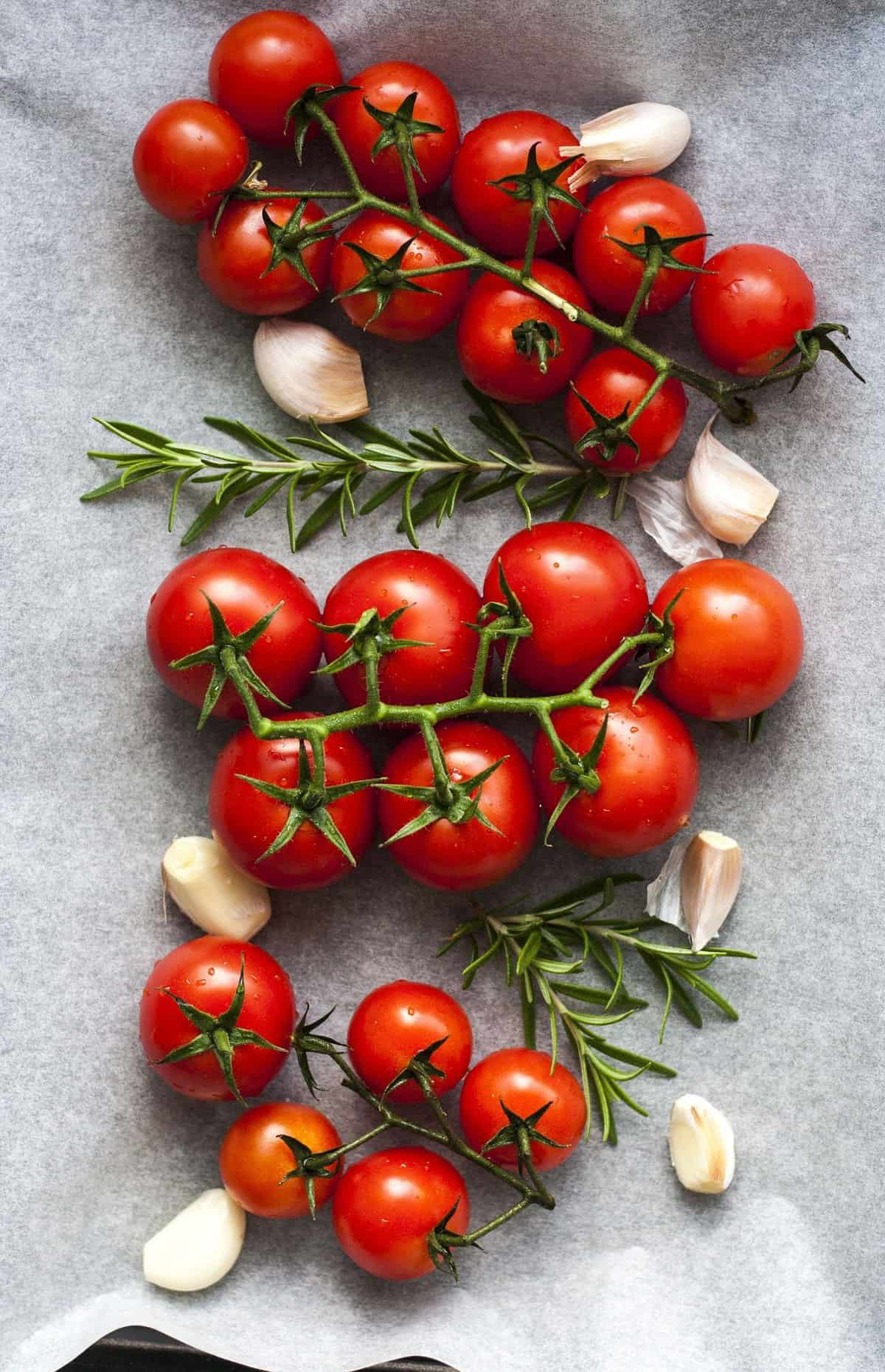 Three bunches of cherry tomatoes and garlic on a parchment paper