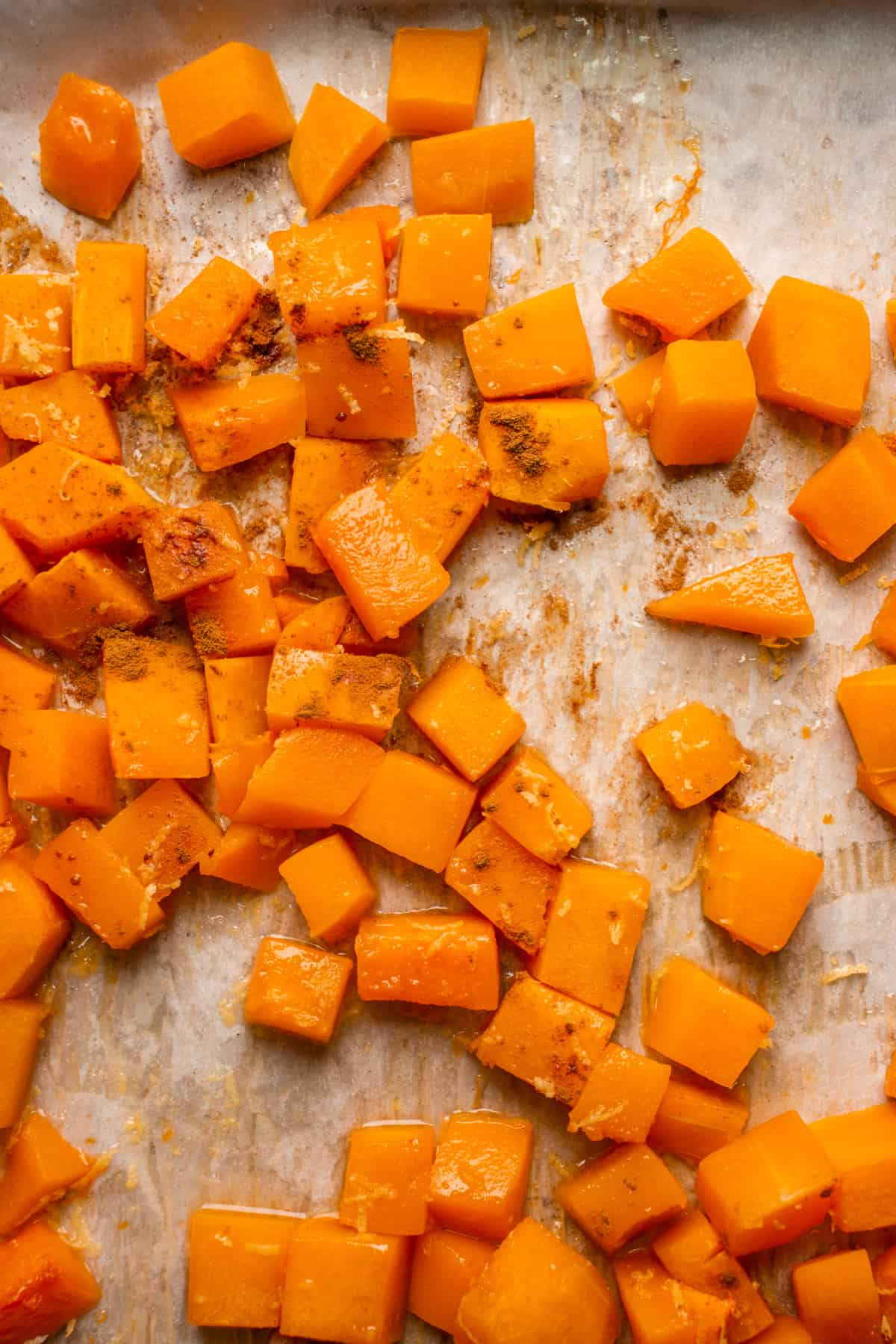 Baked butternut squash with cinnamon and lemon zest on a baking sheet