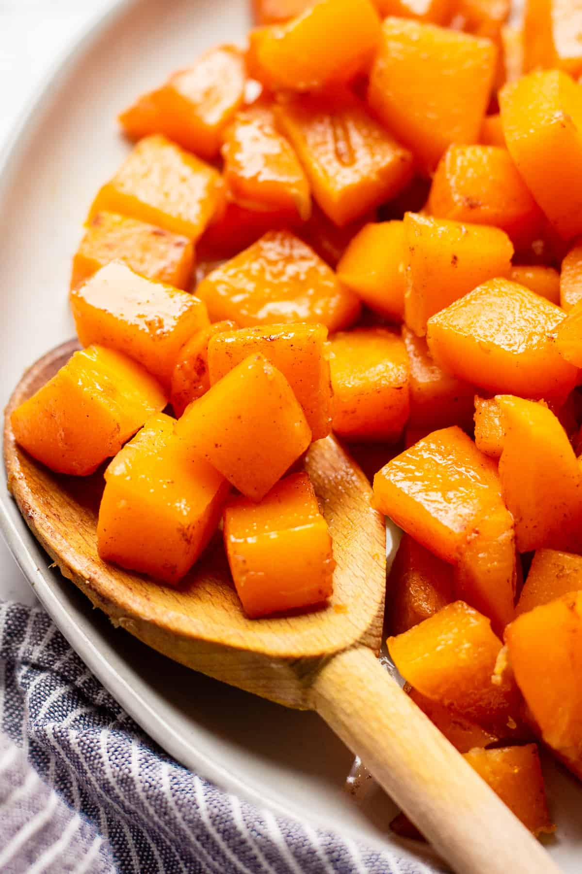 A wooden spoon full of roasted and candied butternut squash