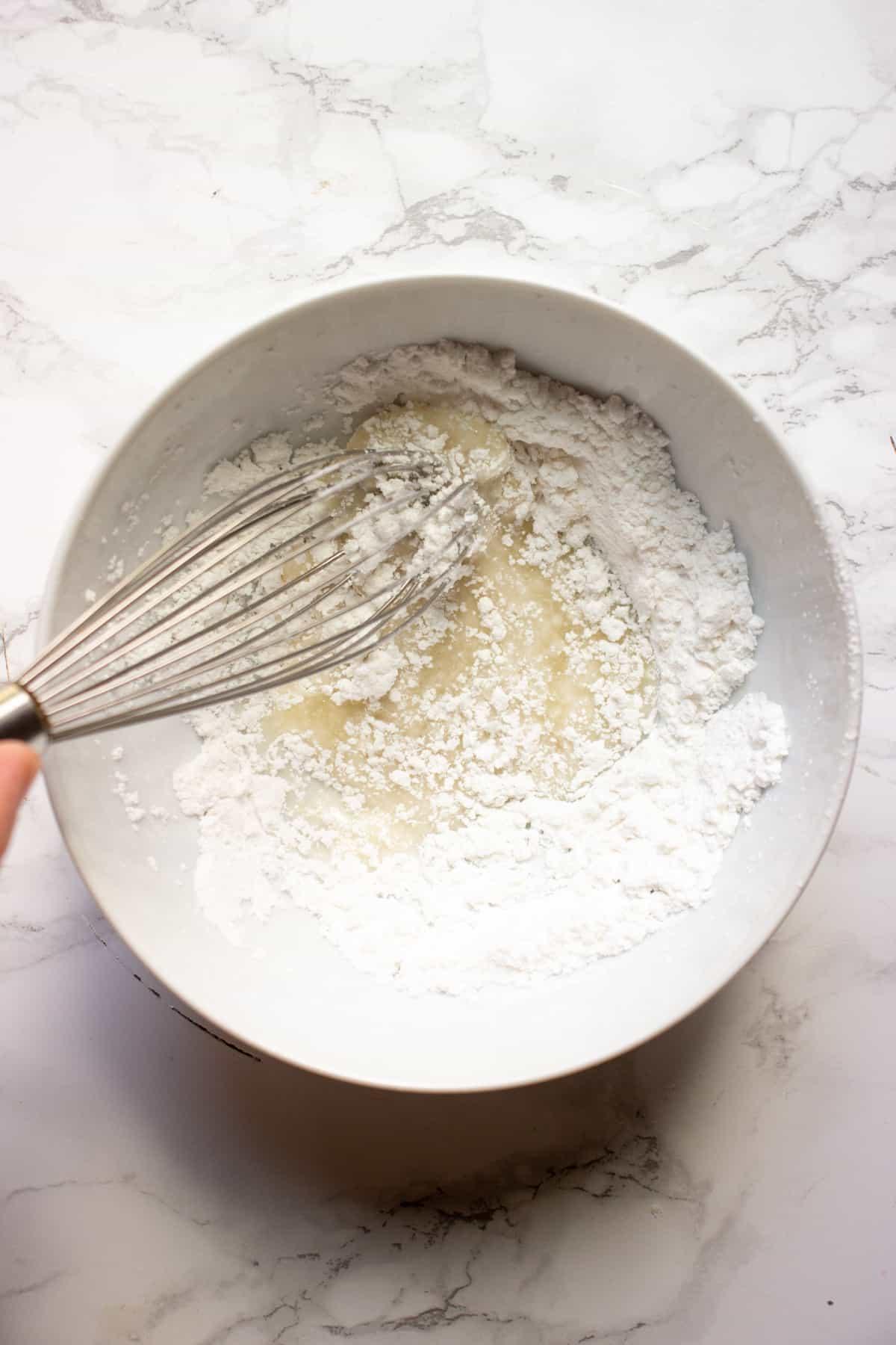 Making a sugar-lemon glaze in a small white bowl