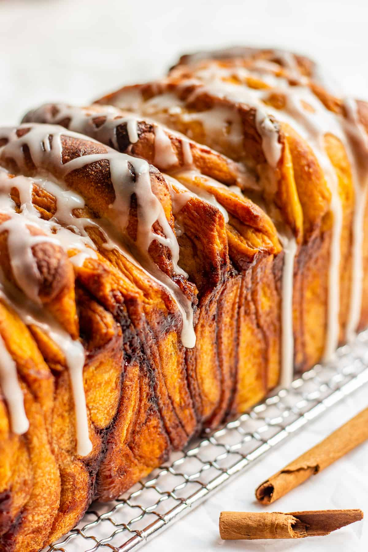 Side shot of a cinnamon sugar pull apart loaf on a wire rack against a white background