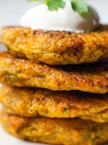 A stack of pumpkin fritters topped with sour cream and fresh parsley