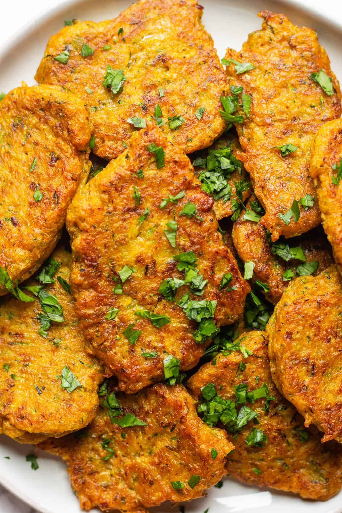 Pumpkin fritters on a white plate sprinkled with parsley