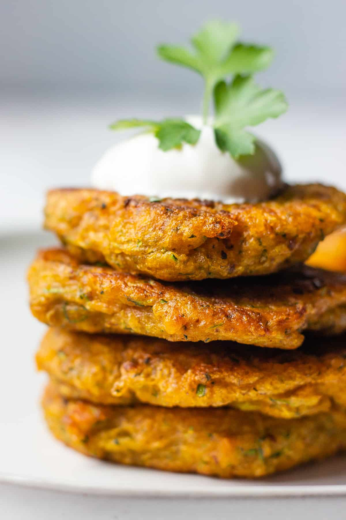 Stack of four pumpkin and zucchini fritters on a white plate against blue background