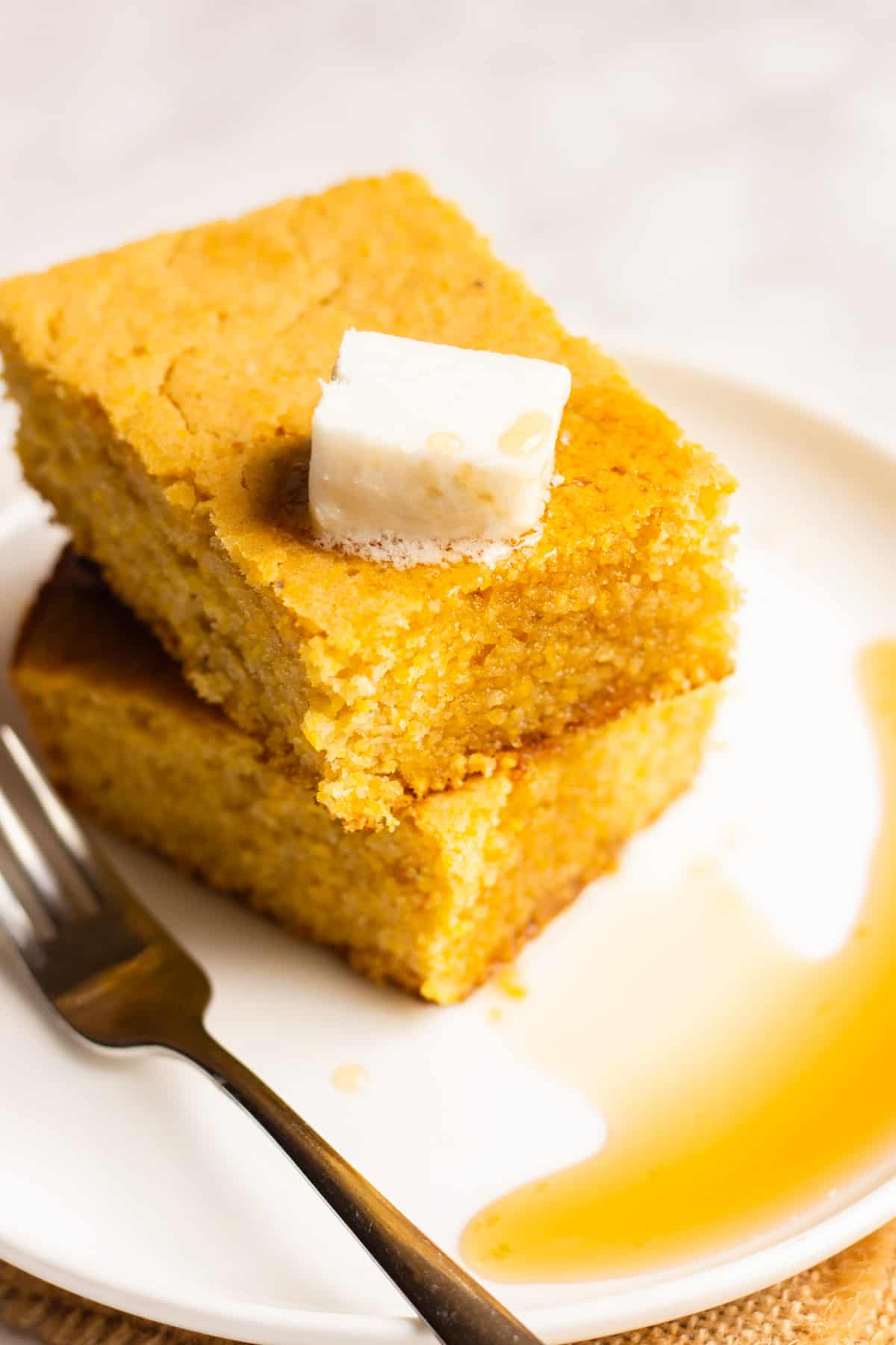 Two square cornmeal breads on a white plate