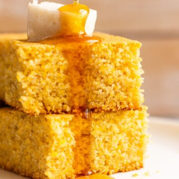Two slices of vegan cornbread recipe topped with butter and Maple syrup