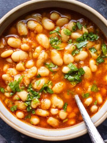 Vegan Moroccan White Bean Stew in a grey bowl on a blue background